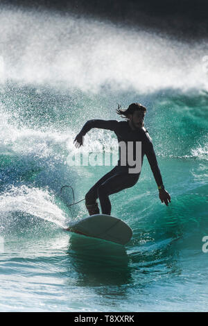 Surfing action as a surfer is silhouetted against the sunlight as rides a wave in a jade coloured sea at Fistral in Newquay in Cornwall. - Stock Image