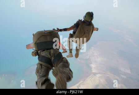 U.S. military members from the 82nd Expeditionary Rescue Squadron perform a training jump out of a C-130J near Camp Lemonnier, Djibouti, on Aug. 25, 2018. The 82nd ERQS maintains high altitude low opening proficiency in order to conduct personnel recovery, casualty evacuation, medical evacuation, and sensitive item recovery within the Combined Joint task Force Horn of Africa Combined Joint Operations area in partnership with the 75th Expeditionary Airlift Squadron. (U.S. Air Force photo by Senior Airman Taylor Harrison) - Stock Image