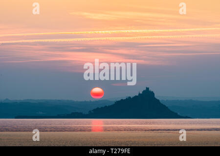 Red sun rising beside St Michaels Mount Cornwall reflecting in the sea - Stock Image