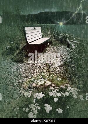 Empty bench in a strange green rainstorm - Stock Image