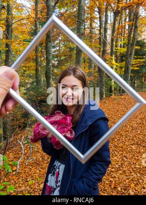 Pretty teen girl is smiling at camera framed by picture flramed hand held before camera - Stock Image