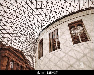 A view from the Great Court looking upwards at the  famous glass and steel roof structure of The British Museum in London, England. To the right is The Reading Room. Photo © COLIN HOSKINS. - Stock Image