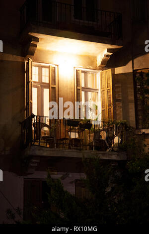 Lit Balcony with table and Chairs  in Tel Aviv, Israel - Stock Image