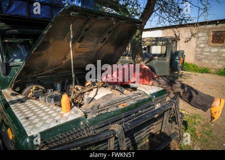 Bush mechanic working on a broken-down four-wheel drive vehicle near Moshi, Tanzania, Africa - Stock Image