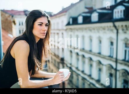 Happy young businesswoman with cup of coffee standing on a terrace in an office in city. Copy space. - Stock Image