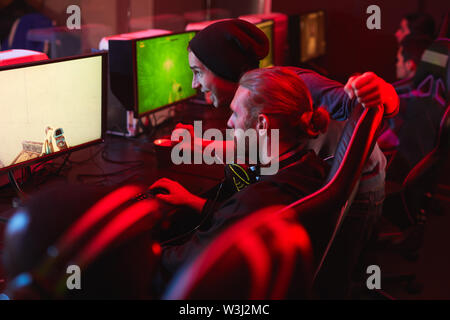 Positive excited hipster guys playing computer game together in modern pc game club - Stock Image
