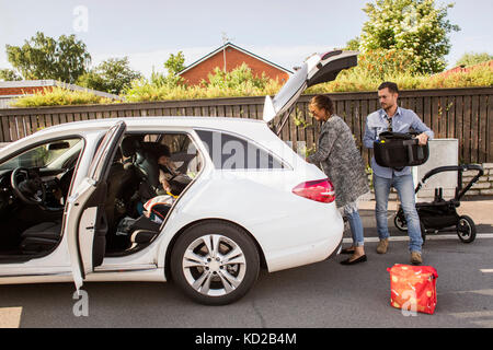 Son (18-23 months) sitting in car and parents packing luggage - Stock Image