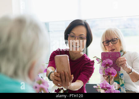 Active senior women with camera phone photographing orchids in flower arranging class - Stock Image