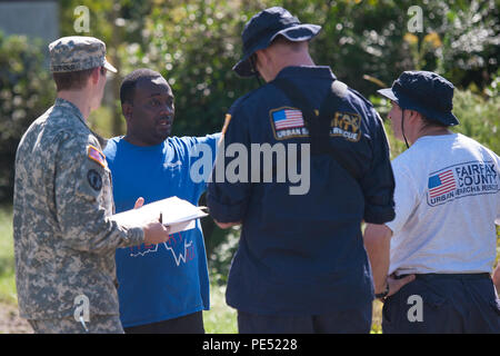 U.S. Army Sgt. Brandon Stafford assigned to the 133rd Military Police Company, S.C. Army National Guard, along with Mike Adams and Sergio Cueto from Virginia Task Force 1, Fairfax County, Va., converse with Clifton Harris of North Santee, S.C., during a health and welfare check Oct. 6, 2015. The health and welfare checks were in response to widespread flooding in the area as a result of heavy rain. The South Carolina National Guard partnered with federal, state and local emergency management agencies and first responders. (U.S. Army National Guard photo by Sgt. Brian Calhoun/Released) - Stock Image