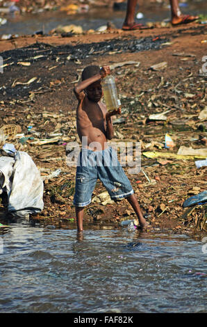 Boy collecting dirty water in Kroo Bay, Sierra Leone. - Stock Image