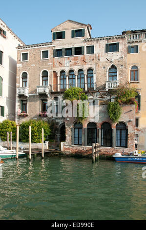 Charming old traditional building house palazzo with flowers and hanging baskets near Rialto on the Grand Canal - Stock Image