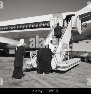 1960s, historical, arab passengers boarding the rear of a Sadsi Arabia Airlines aircraft on the runaway at Jeddah. - Stock Image