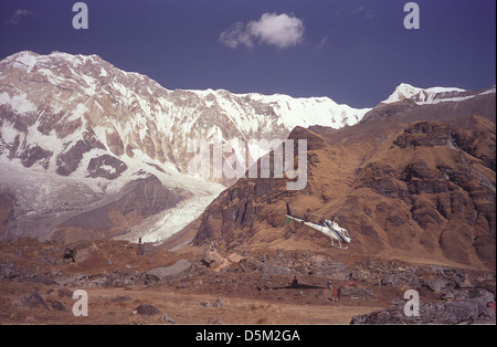 Karnali Helicopter taking off from Annapurna Base Camp with Annapurna I 8091 metres behind Nepal Himalayas - Stock Image