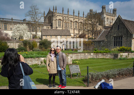 Foreign tourists taske photographs of Christ Church Cathedral, Oxford across the War Memorial Gardens - Stock Image