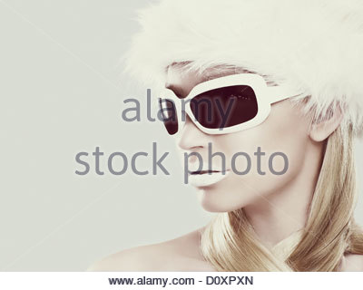 Young woman wearing white sunglasses and fur hat - Stock Image