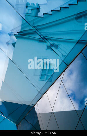 Blue abstract reflection of a traditional Prague turreted building taken from the glass roof of a modern art gallery Czech Republic. - Stock Image