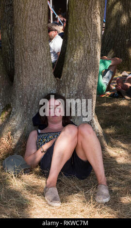 A festival goer has a nap in the woods area of Latitude Festival 2018. - Stock Image