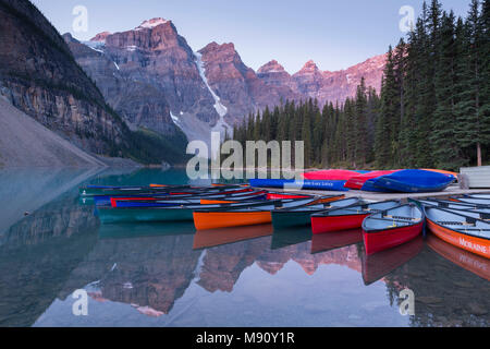 Canoes on Moraine Lake at dawn in the Canadian Rockies, Banff National Park, Alberta, Canada. Autumn (September) 2017. - Stock Image