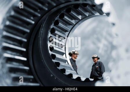 two mechanics inside giant cogwheel and gear - Stock Image