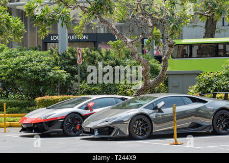 two luxury Lamborghini cars parked outside a shopping mall in central Singapore on Orchard Road - Stock Image