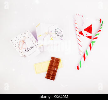 Christmas decoration with square gift box with dark and white chocolate and candy cane for celebration with snow - Stock Image
