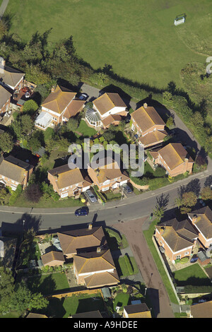 Aerial view of detached housing in small housing estate next to a playing field - Stock Image
