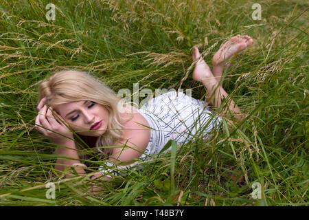 Dreamy young blonde woman relaxing lying down in a meadow with high grasses - Stock Image