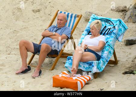 Lyme Regis, Dorset, UK.  13th July 2019. UK Weather.  A couple relaxe on the beach at the seaside resort of Lyme Regis in Dorset on a warm cloudy day.  Picture Credit: Graham Hunt/Alamy Live News - Stock Image