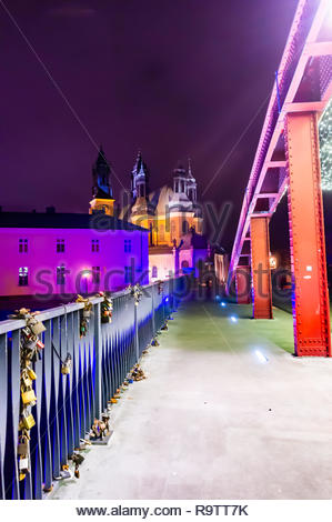 Poznan, Poland - December 26, 2018: Metal barrier on the Jordan bridge by night over the Warta river with cathedral building in the background. - Stock Image