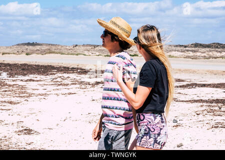 Couple of young people walking at the beach - tourists concept in outdoor leisure activity - blue sky and coloured clothes - Stock Image