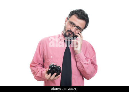 Smiling man with alarm clock talking on smart phone - Stock Image