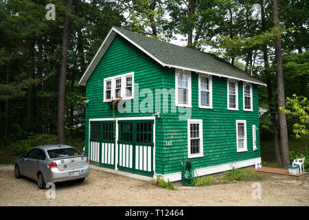 Bright green shingled house with white trimmings and wide double doors, Scarborough, Maine, USA. - Stock Image