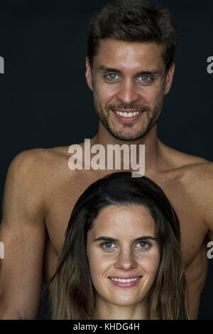 Young couple smiling cheerfully, portrait - Stock Image