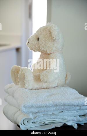Teddy bear on towel in bathroom - Stock Image