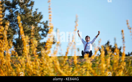 Businessman taking a break at park during daytime - Stock Image