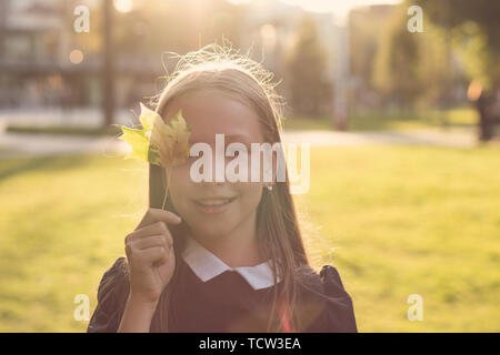 Portrait of european cute teen girl with maple leaf in her hands. She is posing in sunset light and smiling at camera. Face to face. Address blank - Stock Image