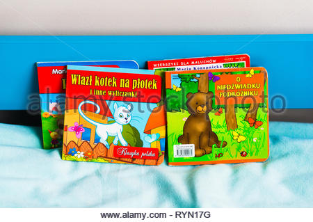Poznan, Poland - November 18, 2018: Colorful Polish books on a blue bed with soft sheet. - Stock Image
