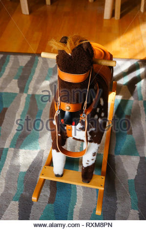 Swing horse standing in a room on a carpet floor. - Stock Image