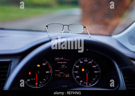 Pair of glasses on dashboard of car - Stock Image