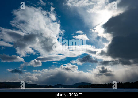 Storm clouds moving in over the sun and covering a deep blue sky with white clouds. - Stock Image