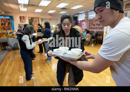 Worshippers at a Buddhist temple form an assembly line delivering food prepared and cooked  for their monks. In Elmhurst, Queens, New York - Stock Image