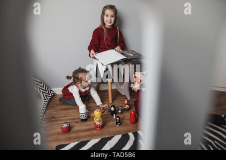 Mother and two girls playing in children's room at home - Stock Image
