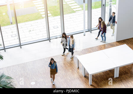 Male and female university students arriving in university lobby, high angle view - Stock Image
