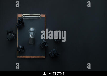 Building and construction concept, the light bulb of an idea on a dark background with black crumpled paper balls and a clipboard. - Stock Image