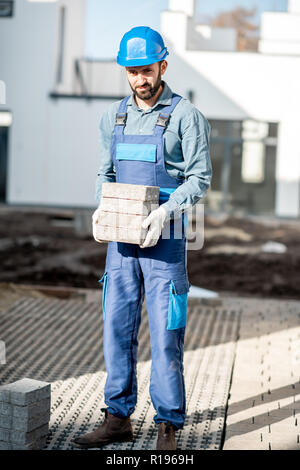 Porait of a builder in uniform holding paving tiles on the construction site with white houses on the background - Stock Image