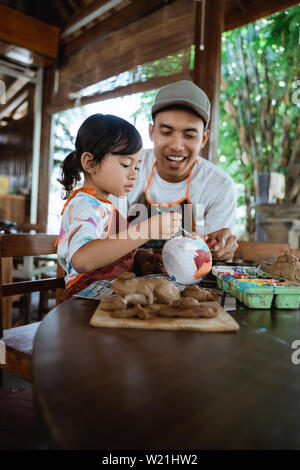 happy father and child painting pottery goods together using brush in workshop - Stock Image