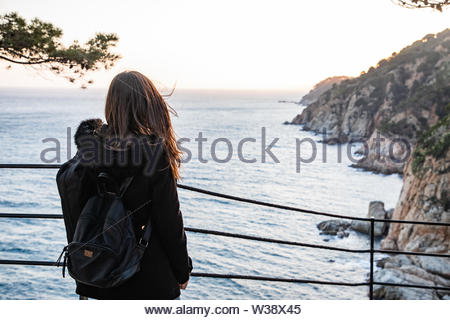 Woman looking at sunset on rocky cliff coastline - Stock Image
