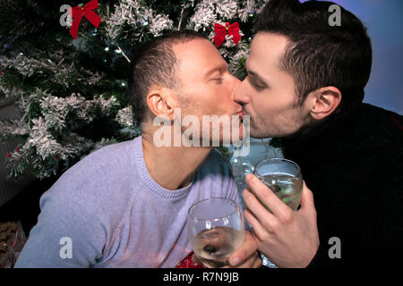 Gay couple celebrating and kissing in front of Christmas tree with glasses of sparkling wine - Stock Image
