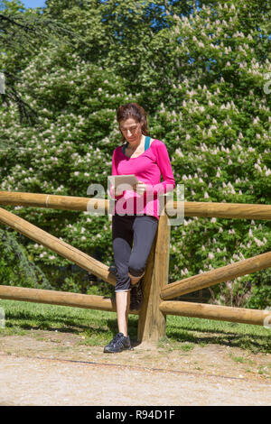 adult woman with pink sweater black knee trousers, watching digital tablet, leaning in wooden fence, in park of Retiro, in Madrid, Spain - Stock Image