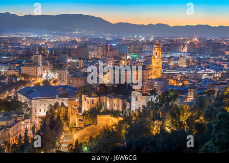 Malaga Cathedral with Old Town scenic view from Gibralfaro with the Alcazaba castle at sunset twilight dusk evening - Stock Image